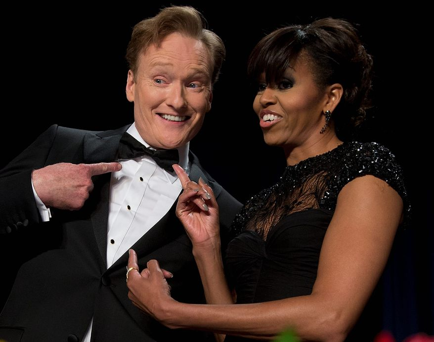 First lady Michelle Obama and late-night television host and comedian Conan O'Brien gesture toward his tie at the White House Correspondents' Association Dinner at the Washington Hilton Hotel on Saturday, April 27, 2013, in Washington. (AP Photo/Carolyn Kaster)