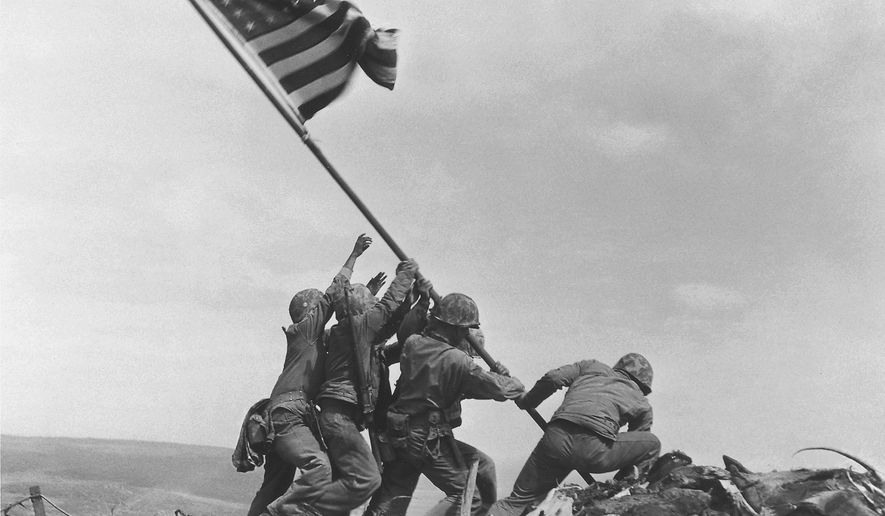 U.S. Marines of the 28th Regiment, 5th Division, raise the American flag atop Mount Suribachi on Iwo Jima on Feb. 23, 1945, in a Pulitzer Prize-winning photo by Associated Press photographer Joe Rosenthal. (AP Photo/Joe Rosenthal)