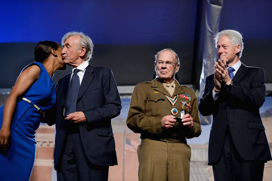 Former President Bill Clinton and World War II veteran Scottie Ooton applaud as U.S. Holocaust Memorial Museum staff member Rebecca Dupas gets a kiss from Elie Wiesel, the museum's founding chairman, in the District on Monday. (Andrew Harnik/The Washington Times)