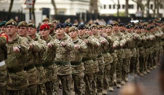 **FILE** Members of the British military's 4th Mechanised Brigade parade through central London to attend a reception at the Houses of Parliament on April 22, 2013. The soldiers recently returned from six months serving in Afghanistan's Helmand province. (Associated Press)