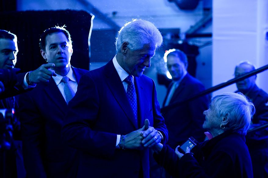 Former President Bill Clinton (center) greets Riki Roussos (right), who slipped beyond the security barrier to meet Mr. Clinton after the U.S. Holocaust Memorial Museum's 20th-anniversary commemoration and national tribute to Holocaust survivors and World War II veterans in Washington on Monday, April 29, 2013. (Andrew Harnik/The Washington Times)
