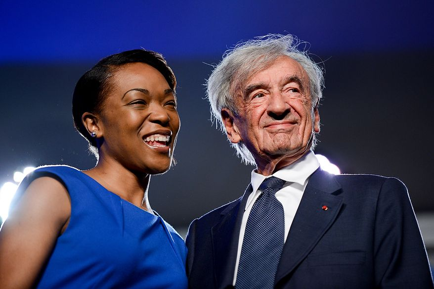 U.S. Holocaust Memorial Museum staff member Rebecca Dupas (left) smiles with Elie Wiesel (right), the museum's founding chairman, as he receives a commemoration pin during the U.S. Holocaust Memorial Museum's 20th-anniversary commemoration and national tribute to Holocaust survivors and World War II veterans in Washington on Monday, April 29, 2013. (Andrew Harnik/The Washington Times)