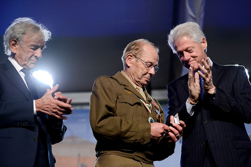 Former President Bill Clinton (right) presents Scottie Ooton (center), a member of the U.S. Army's 84th Infantry Division, which liberated the Hanover-Ahlem Concentration Camp during the Second World War, with a commemoration pin during the U.S. Holocaust Memorial Museum's 20th-anniversary commemoration and national tribute to Holocaust survivors and World War II veterans in Washington on Monday, April 29, 2013. (Andrew Harnik/The Washington Times)
