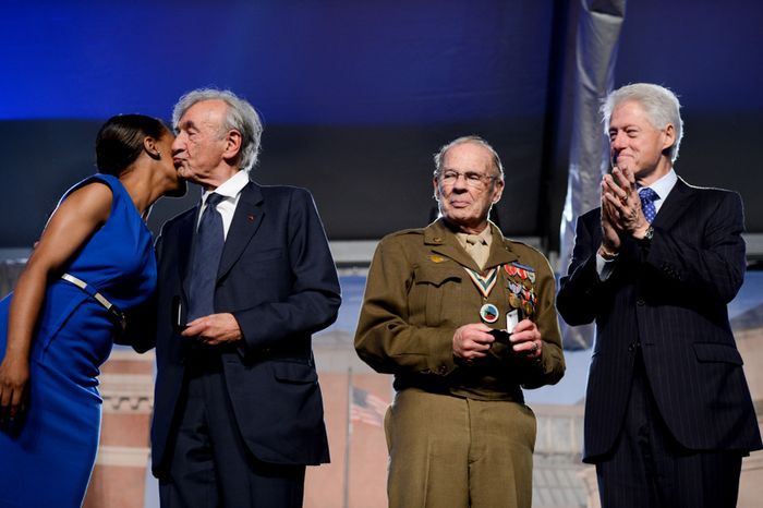 Former President Bill Clinton (right) and Scottie Ooton (second from right), a member of the 84th Infantry Division, which liberated the Hanover-Ahlem Concentration Camp in Germany in World War II, applaud as U.S. Holocaust Memorial Museum staff member Rebecca Dupas (left) gets a kiss from Elie Wiesel, founding chairman of the museum. He and Mr. Ooton were presented with commemoration pins during the U.S. Holocaust Memorial Museum's 20th-anniversary commemoration and national tribute to Holocaust survivors and World War II veterans in Washington on Monday, April 29, 2013. (Andrew Harnik/The Washington Times)