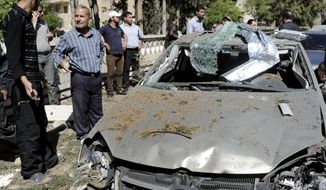 This photo released by the Syrian official news agency SANA, shows Syrians inspecting a damaged car at the scene of a car bomb exploded in the capital's western neighborhood of Mazzeh, in Damascus, Syria, Monday, April. 29, 2013. (AP Photo/SANA)