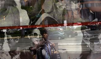 A pedestrian is reflected in a retail store's window display in Baltimore on Thursday, April 25, 2013. (AP Photo/Patrick Semansky)