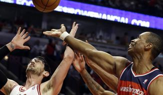 Washington Wizards center Jason Collins (right) battles for a rebound against Chicago Bulls guard Kirk Hinrich during the first half of an NBA basketball game in Chicago on Wednesday, April 17, 2013. Collins has become the first male professional athlete in the four major sports leagues to come out as gay. (AP Photo/Nam Y. Huh)