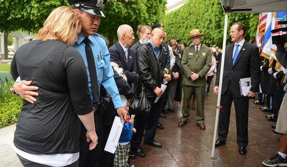 Prince William County Police Officer Dale Yung is comforted by his wife Nancy, left, during a ceremony to unveil the name of his brother, slain Prince William County Police Officer Chris Yung on the wall of the National Law Enforcement Memorial, Washington, D.C., Monday, April 29, 2013. Yung was killed in a motorcycle accident while responding to a separate car crash New Years Eve last year. (Andrew Harnik/The Washington Times)