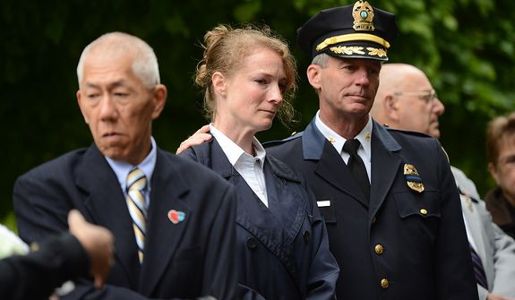 Robin Yung, center, is comforted by Prince William County Police Chief Steve Hudson, right, during a ceremony to unveil the name of her slain husband, Prince William County Police Officer Chris Yung on the wall of the National Law Enforcement Memorial, Washington, D.C., Monday, April 29, 2013. Yung was killed in a motorcycle accident while responding to a separate car crash New Years Eve last year. Also pictured is Yung's father, Edward Yung, left. (Andrew Harnik/The Washington Times)