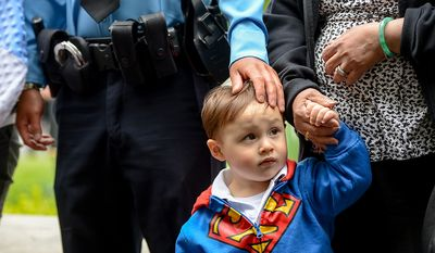 Patrick Yung, 2, stands next to his father, Officer Dale Yung, left, during a ceremony to unveil the name Dale's brother, slain Prince William County Police Officer Chris Yung on the wall of the National Law Enforcement Memorial, Washington, D.C., Monday, April 29, 2013. Yung was killed in a motorcycle accident while responding to a separate car crash New Years Eve last year. (Andrew Harnik/The Washington Times)