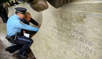 Prince William's County Police Officer Dale Yung and Brian Yung make a rubbing of their slain brother, Prince William County Police Officer Chris Yung during a ceremony to unveil his name on the wall of the National Law Enforcement Memorial, Washington, D.C., Monday, April 29, 2013. Yung was killed in a motorcycle accident while responding to a separate car crash New Years Eve last year. (Andrew Harnik/The Washington Times)