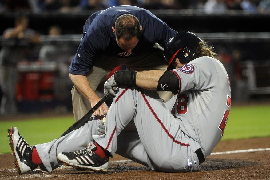 Jayson Werth is visited by Washington Nationals trainer Lee Kuntz after fouling a ball into his left ankle Monday night. (Associated Press photo)