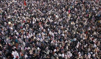 Pakistani Shiite Muslims sit in protest in Quetta, Pakistan, on Monday, Feb. 18, 2013, following a bombing that killed scores of people on Saturday. The protesters have refused to bury victims of the attack until authorities take action against the militants who were responsible. (AP Photo/Arshad Butt)