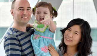 **FILE** Hannah Warren, 2, poses with her parents Lee Young-mi and Darryl Warren at Seoul National University Hospital in Seoul on July 13, 2012. Hannah, who was born without a windpipe, received a new windpipe made from her own stem cells in a landmark operation on April 9, 2013, at Children's Hospital of Illinois in Peoria, Ill. She is the youngest patient ever to get the experimental treatment. (Associated Press/The Korea Herald)
