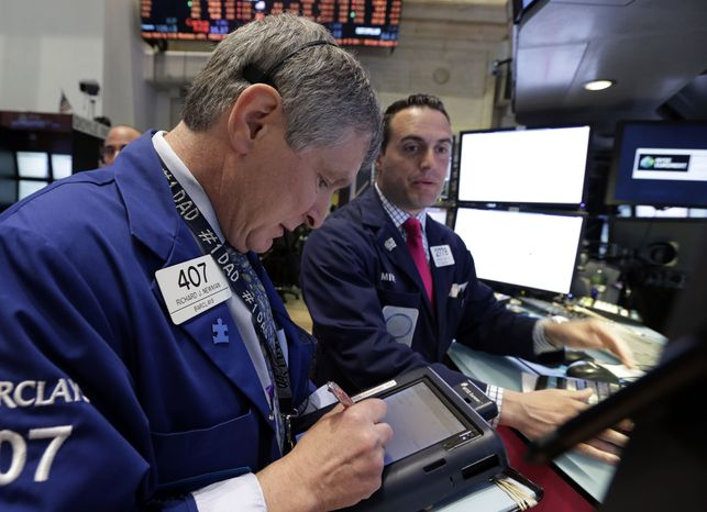 Trader Richard Newman (left) works on the floor of the New York Stock Exchange on May 1, 2013. (Associated Press)