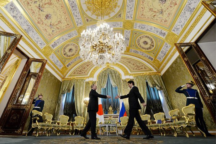 Russian President Vladimir Putin shakes hands with Japanese Prime Minister Shinzo Abe during a meeting in Moscow on Monday. It was the first Russian visit by a Japanese prime minister in 10 years. (Associated Press)