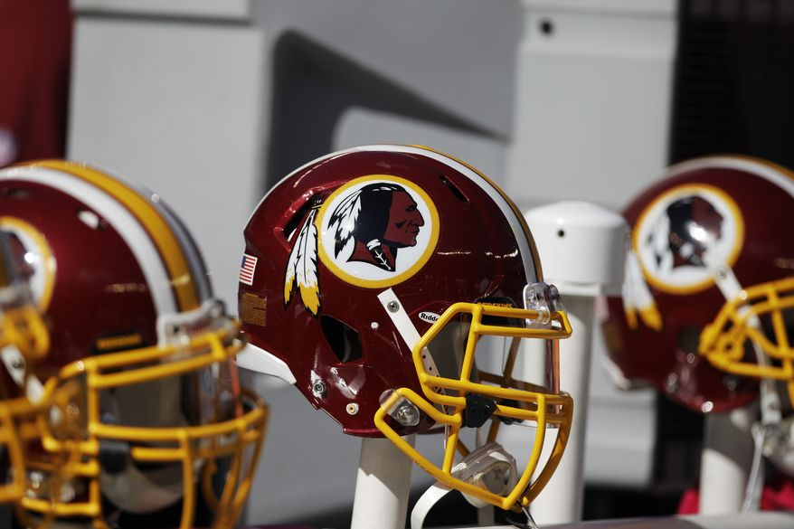 Washington Redskins helmets and logo are shown during the first half of an NFL football game in East Rutherford, N.J. on Oct. 21, 2012. The team's nickname, which some consider a derogatory term for Native Americans, has faced a barrage of criticism. Local leaders and pundits have called for a name change. (Associated Press) **FILE**