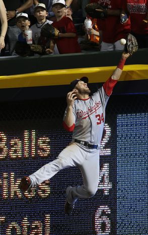 Washington Nationals center fielder Bryce Harper can't catch a home run by Atlanta Braves pitcher Tim Hudson in the fifth inning of a baseball game Tuesday, April 30, 2013, in Atlanta. (AP Photo/John Bazemore)