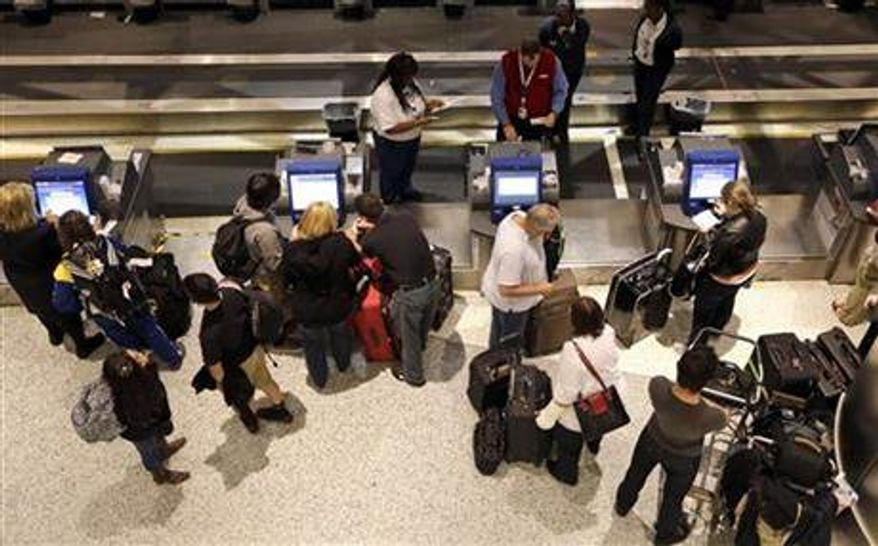 ** FILE ** Airline passengers check-in at George Bush Intercontinental Airport Tuesday, Nov. 20, 2012, in Houston. Americans can expect airports to be busier and planes to be fuller than ever, according to a forecast by the main trade association for U.S. airlines released ahead of the holiday. (AP Photo/David J. Phillip