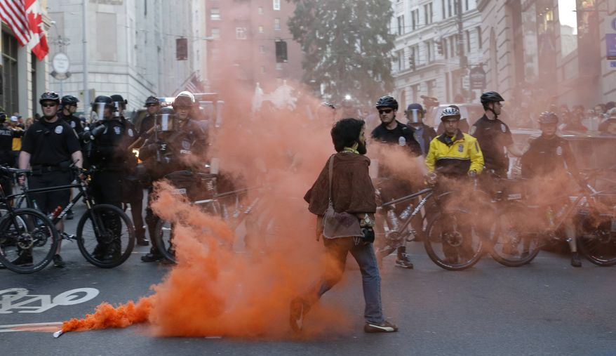 A protester walks away after placing a smoke device on the ground in front of police officers during a May Day march that began as an anti-capitalism protest and turned into demonstrators clashing with police on Wednesday, May 1, 2013, in downtown Seattle. (AP Photo/Ted S. Warren)