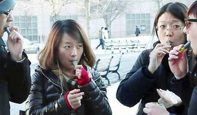 **FILE** Students try samples of AeroShot, an inhalable caffeine, from a lipstick-sized canister on the campus of Northeastern University in Boston. The FDA will review the safety and legality of the advertised dietary supplement. (Associated Press)