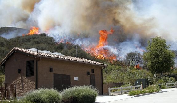 Smoke and fire billows over a hill near Thousand Oaks, Calif. on Thursday, May 2, 2013. Authorities have ordered evacuations of a neighborhood and a university about 50 miles west of Los Angeles where a wildfire is raging close to subdivisions. T. (AP Photo/Nick Ut)