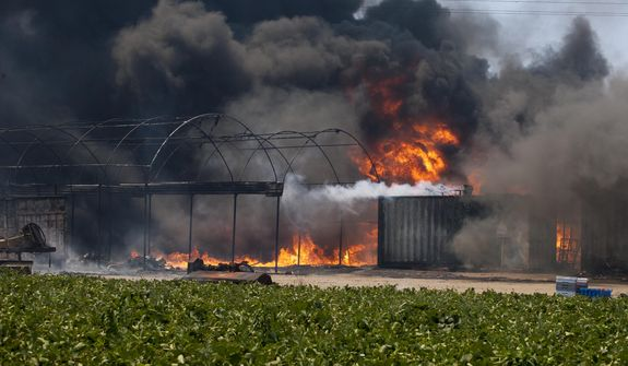 Flames and smoke rise from chemical storage tanks near a strawberry farm in Camarillo, Calif., Thursday, May 2, 2013. (AP Photo/Ringo H.W. Chiu)