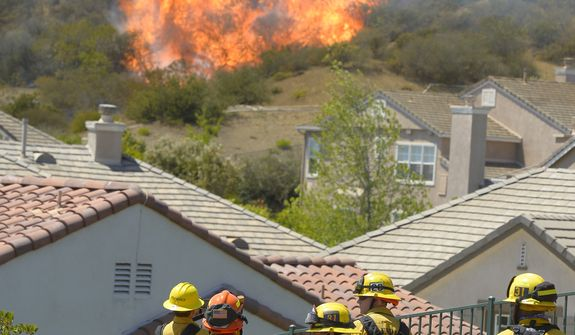 Firefighter looks on as fire burns behind homes during a wildfire that burned several thousand acres, Thursday, May 2, 2013, in Thousand Oaks, Calif.   (AP Photo/Mark J. Terrill)