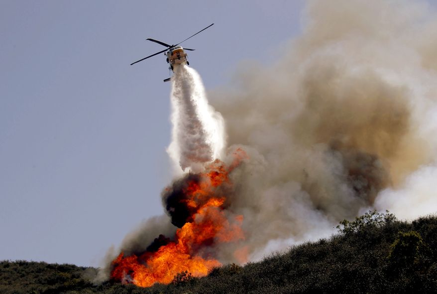 A helicopter makes a water drop on a hotspot over a hill near Thousand Oaks, Calif. on Thursday, May 2, 2013. Authorities have ordered evacuations of a neighborhood and a university about 50 miles west of Los Angeles where a wildfire is raging close to subdivisions. The blaze on the fringes of Camarillo and Thousand Oaks broke out Thursday morning and was quickly spread by gusty Santa Ana winds. Evacuation orders include California State University, Channel Islands. (AP Photo/Nick Ut)