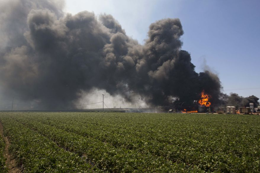 Flames and smoke rise from chemical storage tanks near a strawberry farm in Camarillo, Calif., Thursday, May 2, 2013. A wildfire fanned by gusty Santa Ana winds raged along the fringes of Southern California communities on Thursday, forcing evacuation of homes and a university while setting recreational vehicles ablaze. (AP Photo/Ringo H.W. Chiu)