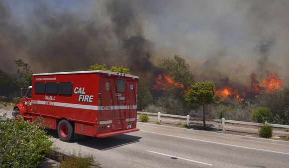 A fire vehicle stands by as a wildfire burns along a roadside in Thousand Oaks, Calif., Thursday, May 2, 2013. A Ventura County Fire Department spokeswoman said the blaze that broke out Thursday morning near Camarillo and Thousand Oaks, 50 miles west of Los Angeles, had spread to over 6,500 acres, forcing evacuations of nearby neighborhoods. (AP Photo/Mark J. Terrill)