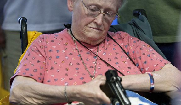NRA attendee Janet Bero waits to have her German Luger appraised during the NRA's Antiques Guns and Gold Showcase during the National Rifle Association's 142 Annual Meetings and Exhibits at the George R. Brown Convention Center in Houston on May 2, 2013. (Associated Press/Houston Chronicle) ** FILE **