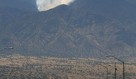 Traffic passes on U.S. 550 as smoke billows from a wildfire burning in the Sandia Mountains near Bernalillo, N.M., on Thursday, May 2, 2013. (AP Photo/Susan Montoya Bryan)