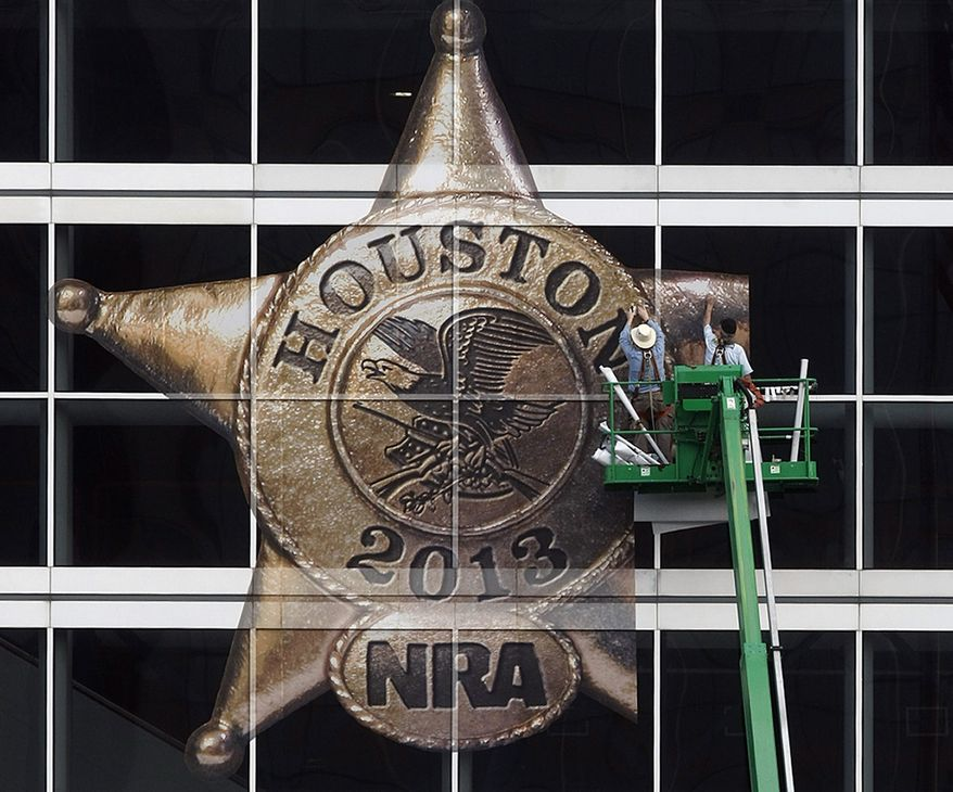 The National Rifle Association's 142 Annual Meetings and Exhibits logo is placed on the George R. Brown Convention Center by Lynn Creel, left, and Don Reynolds of Display Graphics Wednesday, May 1, 2013, in Houston.   The nation's chief gun rights lobby is gathering in Houston this  weekend for its annual convention    (AP Photo/Houston Chronicle,Johnny Hanson )