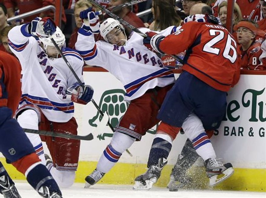 New York Rangers left wing Rick Nash, left, right wing Mats Zuccarello, center, and Washington Capitals center Matt Hendricks battle along the boards for control of the puck during the first period in Game 2 of an NHL hockey Stanley Cup first-round playoff series, Saturday, May 4, 2013, in Washington. (AP Photo/Evan Vucci)
