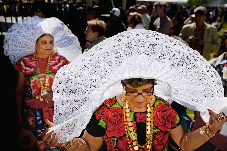 Sisters Emma Gonzalez, center, and Martha Montero [cq], left, originally from of Wahaca, Mexico wear traditional tehuanas clothing at the annual Cinco de Mayo celebration on the National Mall, Washington, D.C., Sunday, May 5, 2013. (Andrew Harnik/The Washington Times)