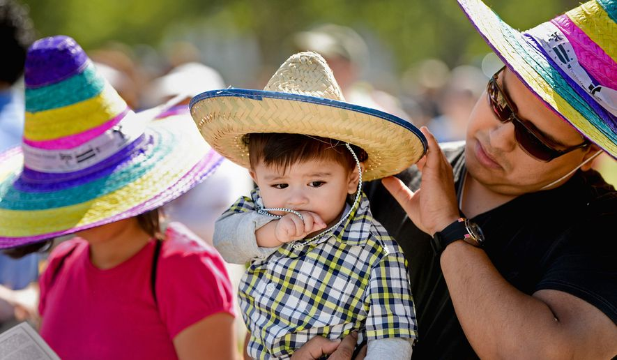 Erick Doledo of Woodbridge, Va., holds his son Erick Jr., and listens live music with his daughter Samantha, 12, left, during the annual Cinco de Mayo celebration on the National Mall, Washington, D.C., Sunday, May 5, 2013. (Andrew Harnik/The Washington Times)
