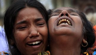 A woman is comforted as she grieves after identifying the body of her daughter, a victim of the garment factory collapse, on Sunday, May 5, 2013, in Savar, near Dhaka, Bangladesh. (AP Photo/Wong Maye-E)