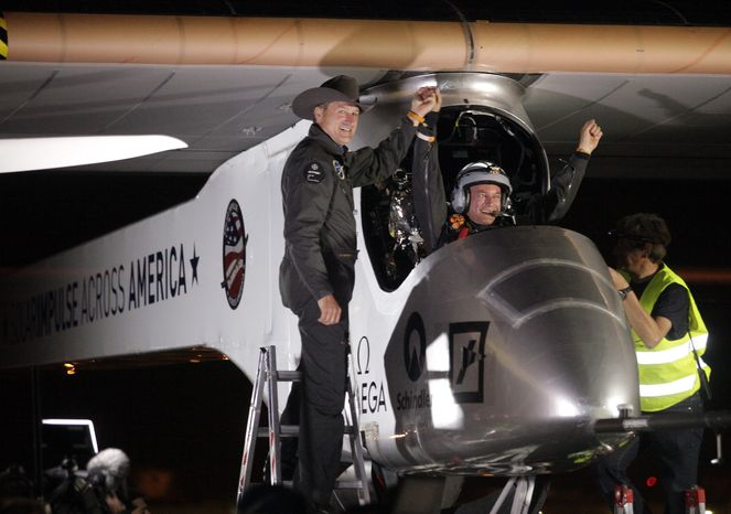 Andre Borschberg (left), Solar Impulse co-founder, CEO and pilot, greets pilot Bertrand Piccard at Sky Harbor International Airport in Phoenix early on Saturday, May 4, 2013, after Mr. Piccard completed the first leg of the Solar Impulse aircraft's coast-to-coast flight. (AP Photo/Scuteri)