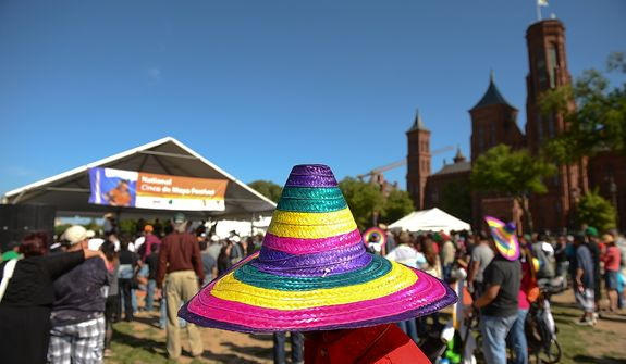 A woman wears a colorful Mexican hat at the annual Cinco de Mayo celebration on the National Mall in Washington on Sunday, May 5, 2013. (Andrew Harnik/The Washington Times)
