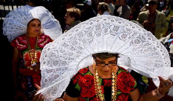Sisters Emma Gonzalez (center) and Martha Montero (left), originally from Wahaca, Mexico, wear traditional tehuanas clothing at the annual Cinco de Mayo celebration on the National Mall in Washington on Sunday, May 5, 2013. (Andrew Harnik/The Washington Times)
