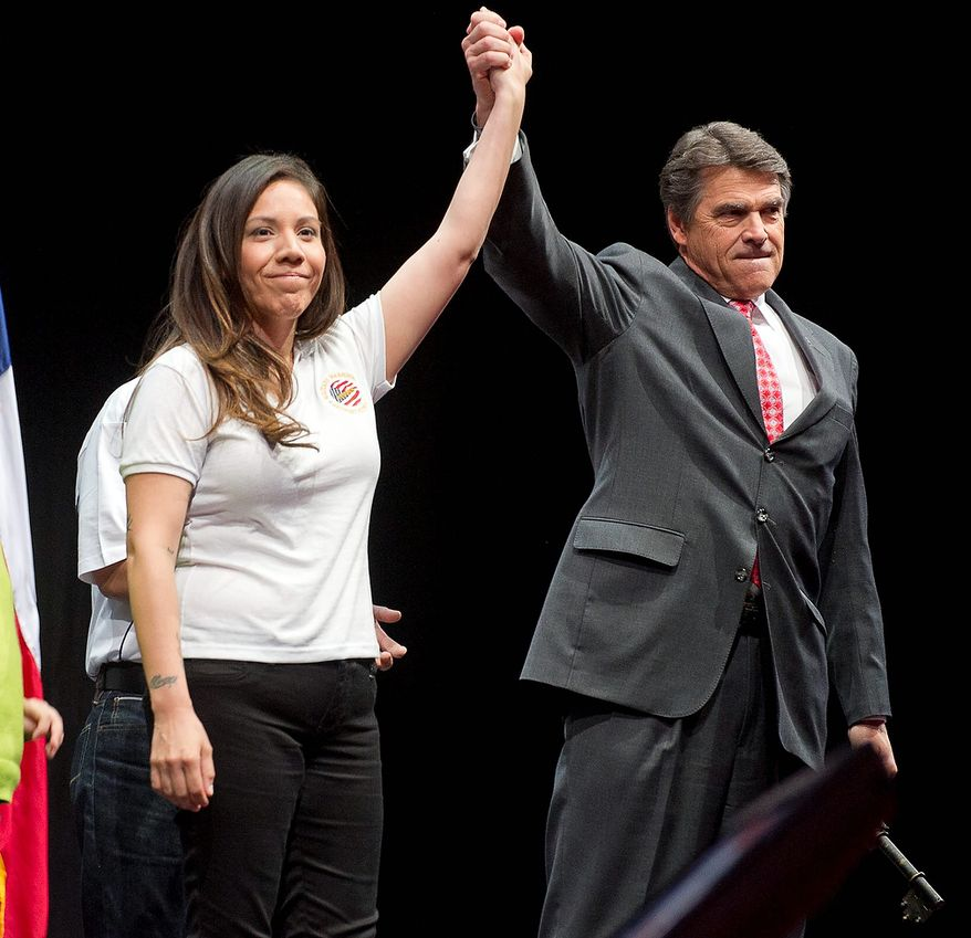 Patricia Aquino is presented the ceremonial key to a new house by  Texas Gov. Rick Perry during the leadership forum at the National Rifle Association's  annual convention Friday, May 3, 2013 in Houston. (AP Photo/Steve Ueckert)
