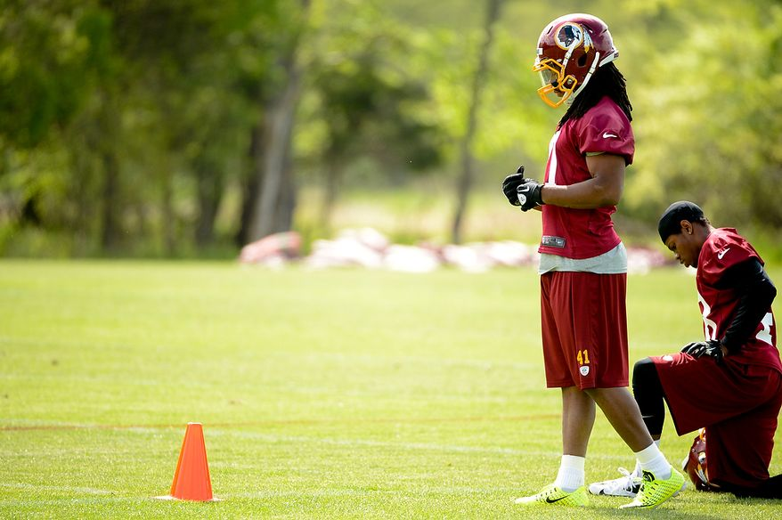 Newly drafted Washington Redskins safety Phillip Thomas (second from right) watches scrimmage drills from the sidelines at the team's rookie minicamp at Redskins Park in Ashburn, Va., on Sunday, May 5, 2013. (Andrew Harnik/The Washington Times)