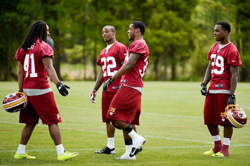 Newly drafted Washington Redskins safety Phillip Thomas (left), cornerback David Amerson (second from right) and safety Bacarri Rambo (right) talk on the sidelines during the team's rookie minicamp at Redskins Park in Ashburn, Va., on Sunday, May 5, 2013. Also pictured is tryout cornerback Akeem Auguste (second from left). (Andrew Harnik/The Washington Times)
