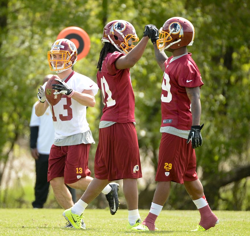 Newly drafted Washington Redskins safety Phillip Thomas (center) and safety Bacarri Rambo (right) high-five each other during a scrimmage at the team's rookie minicamp at Redskins Park in Ashburn, Va., on Sunday, May 5, 2013. (Andrew Harnik/The Washington Times)