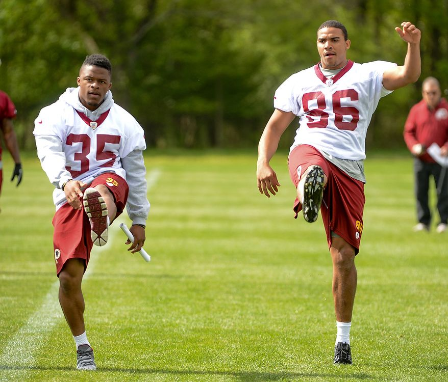 Newly drafted Washington Redskins running back Chris Thompson (left) and tight end Jordan Reed (right) stretch at the team's rookie minicamp at Redskins Park in Ashburn, Va., on Sunday, May 5, 2013. (Andrew Harnik/The Washington Times)