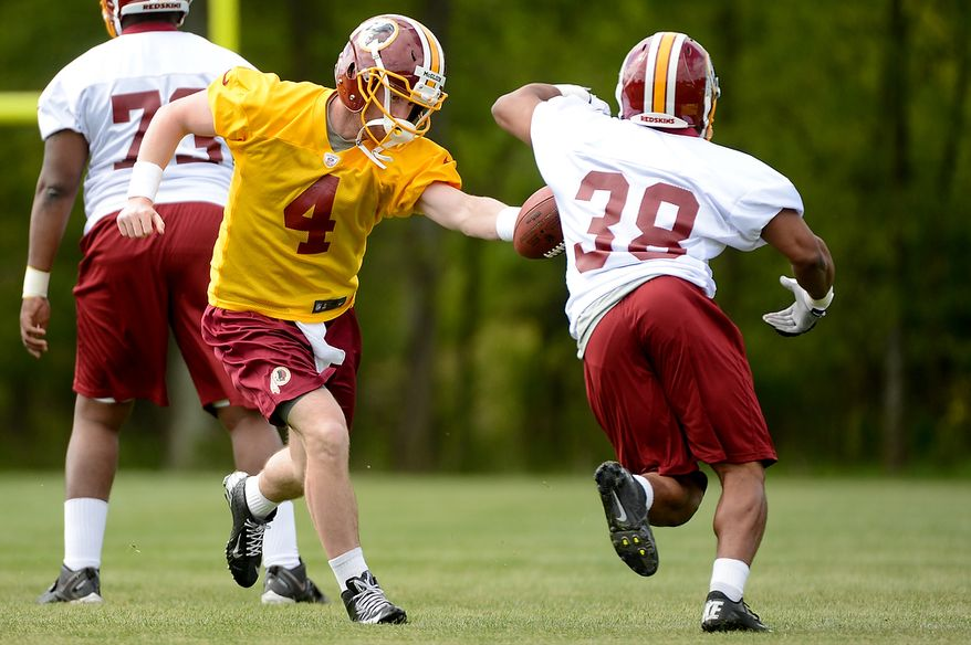Quarterback Matthew McGloin (4) hands off to running back Shawn Morris (38) at the Washington Redskins' rookie minicamp at Redskins Park in Ashburn, Va., on Sunday, May 5, 2013. (Andrew Harnik/The Washington Times)