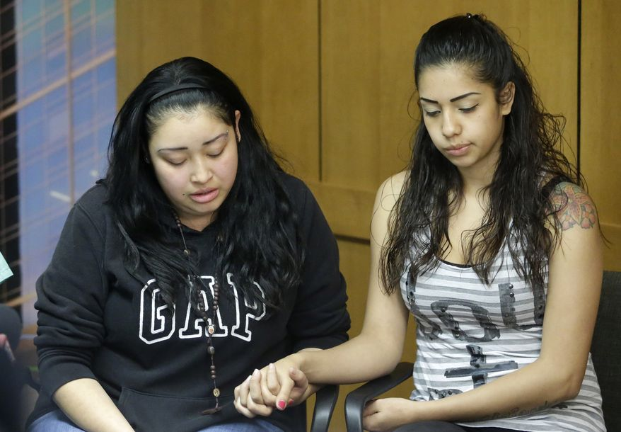 Johana Portillo (left) and her sister Ana Portillo, daughters of soccer referee Riccardo Portillo, hold hands during a news conference on Thursday, May 2, 2013, at the Intermountain Medical Center in Murray, Utah. (AP Photo/Rick Bowmer)