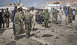 Soldiers gather at the scene of a suicide car bomb blast in Mogadishu, Somalia, on Sunday, May 5, 2013. (AP Photo/Farah Abdi Warsameh)