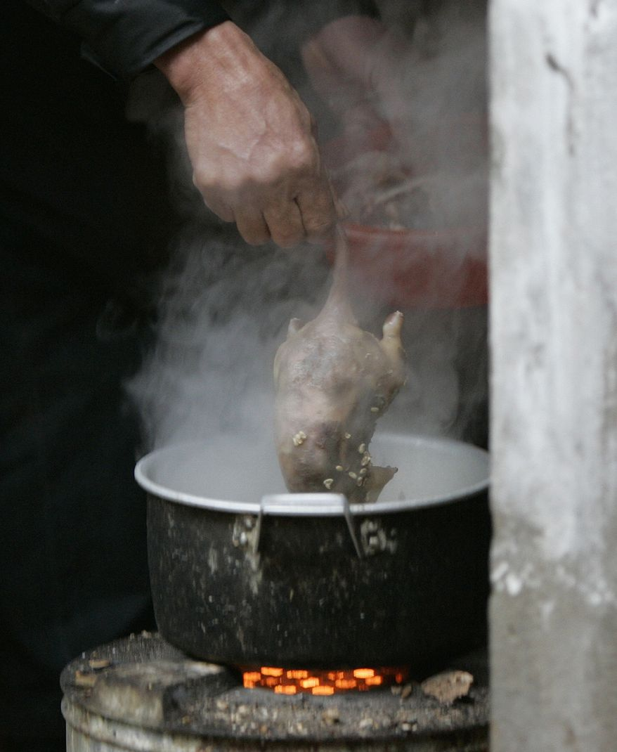**FILE** Nguyen Kim Hung cooks a rat at his home in Dinh Bang Village, Bac Ninh Province, Vietnam, on Jan. 30, 2008. (Associated Press)